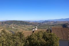 Aerial view of Andalusian scenery with a view of Malaga. Orange tiled rooftops with trees in casarabanela overlooking the andalusian countrye with a distant view Royalty Free Stock Photos