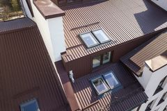 Aerial view of annex room exterior with plastic attic windows, roof and walls covered with brown metal decorative siding planks.  royalty free stock photos