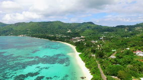 Aerial view of Anse Royale beach with clear sea water of Indian Ocean and green luxuriant hills of Mahe Island, Seychelles, 4k UHD stock footage