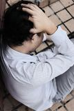 Aerial view of anxious depressed young Asian business man sitting and touching forehead with hands stock image