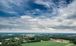 Aerial view of an area of arable land at the edge of a village with connected forest areas and trees along a road in Germany, dram. Atic sky, made with drone Royalty Free Stock Image