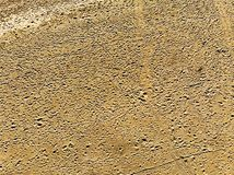 Aerial view of aridity desert pink sand studded with footprints and tire tracks. Aerial view of desert pink sand studded with footprints and tire tracks hits by royalty free stock images