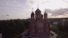 Aerial view of Ascension Cathedral in Lukino Village, Russia. Aerial - Ascension Cathedral and Holy Cross Monastery in Lukino Village. View among green trees in stock footage