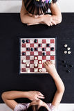 Aerial view of Asian Chinese little sisters playing chess togeth. Er in the living room at home Royalty Free Stock Images