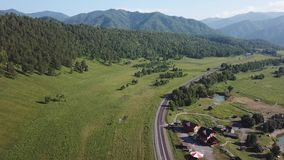 Aerial view of an asphalted winding road in the mountains of the Altai among a green field with trees and a turquoise river near a stock video footage