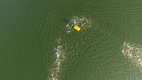 Aerial view of athlete swimmers swimming race on river slow motion. Aerial view of athlete swimmers swimming race in river slow motion. open water triathlon long stock video