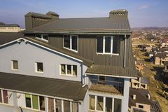 Aerial view of attic annex room exterior with plastic windows, roof and walls covered with brown metal decorative siding planks,. New gutter system on top of stock photo