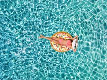 Aerial view of an attractive girl floating over turquoise waters on a donut shaped float. And enjoying the summer sun and holidays royalty free stock images