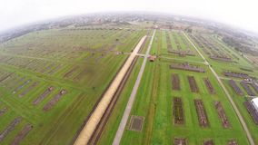 Aerial view of Auschwitz I - Birkenau, living quarters, watch tower and fence stock footage