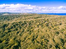 Aerial view of Australian countryside with wind farm in the distance on bright summer day. Stock Images
