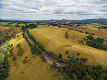 Aerial view of Australian coutryside - yellow fields, hills, and Stock Image