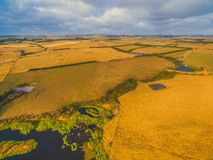 Rural scenery - yellow pastures and hills at sunset. Aerial view of Australian rural scenery - yellow pastures and hills at sunset Royalty Free Stock Image