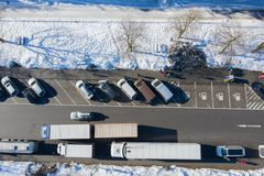 Aerial view of automobile parking lot with cars near highway in winter with snow stock images