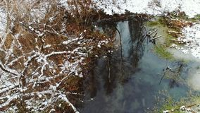Aerial view autumn forest. Interseasonal landscape, flying above forest lake after first snow with reflection stock footage