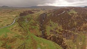 Aerial view of the B4391 through the moor and mountains of Wales close to waterfall, United Kingdom. Aerial view of the B4391 through the moor and mountains of stock footage