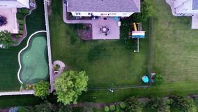 Aerial view of backyard putting green from in air flight above ground stock video