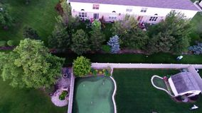 Aerial view of backyard putting green from in air flight above ground stock footage