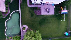 Aerial view of backyard putting green from in air flight above ground stock video footage
