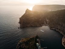 Aerial view of Balaklava bay in Crimea at sunset, mountain cliffs and sea port. Beautiful nature panorama landscape. Summer travel. Concept royalty free stock photos