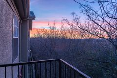 Park side apartment complex balcony during winter sunrise with dramatic clouds. Aerial view from balcony of typical park side apartment complex during winter stock image