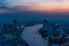 Aerial view of Bangkok cityscape at dusk. With Chao Phraya river. Modern urban background Royalty Free Stock Image