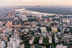 Aerial view of Bangkok modern office buildings, condominium in Bangkok city downtown at the dusk. With golden and purple sky.  Stock Photo