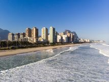 Aerial view of Barra da Tijuca beach during late afternoon with foamy waves. Rio de Janeiro, Brazil. Aerial view of Barra da Tijuca beach during sunset, golden stock photo