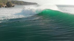 Aerial view of barrel wave in ocean and surfers. Surfing and waves