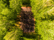 Aerial view of basketball field on day time in forest. Above with drone. Royalty Free Stock Images