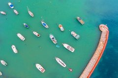 Aerial view of the bay with turquoise water and many small fishing boats with jetty and lighthouse.  royalty free stock images