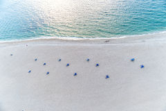 Aerial view on beach with chair, sand, sea, water, people. Aerial view on beach with blue chair, umbrellas on sand near sea, ocean blue water with people on Royalty Free Stock Photo