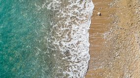 Aerial view of beach with ocean waves reaching shore. Beautiful turquoise water. royalty free stock photos