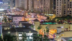Aerial view of beach and tourists walking in JBR with skyscrapers night timelapse in Dubai, UAE. Aerial view of beach and tourists walking in JBR with stock footage