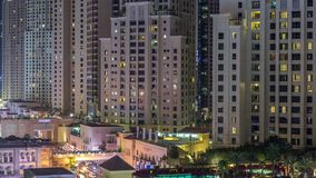 Aerial view of beach and tourists walking in JBR with skyscrapers night timelapse in Dubai, UAE. Aerial view of beach and tourists walking in JBR with stock video