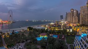 Aerial view of beach and tourists walking in JBR with skyscrapers day to night timelapse in Dubai, UAE. Aerial view of beach and tourists walking in JBR with stock footage
