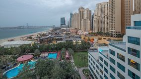 Aerial view of beach and tourists walking in JBR with skyscrapers day to night timelapse in Dubai, UAE. Aerial view of beach and tourists walking in JBR with stock video footage