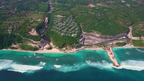 Aerial view of beach with turquoise ocean waves, road, villas on cliff in green. Aerial view of beach with turquoise ocean waves, road and villas on cliff in stock video