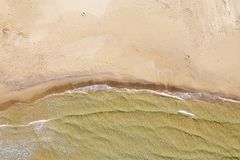 Aerial view of a beach with waves. Crashing with calm sea stock image