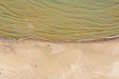 Aerial view of a beach with waves. Crashing with calm sea stock photo
