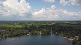 Beatifull lake, field and forest, country summer clouds background. Aerial view of beatifull lake, field and forest. Flying with drone above lake field and stock video footage