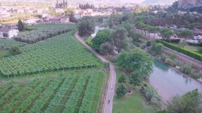 Aerial view of beautiful agricultural fields near river and villages, camera is following two bicyclists. Moving over road stock footage