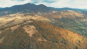 Aerial View of beautiful autumn mountain landscape. Aerial View over beautiful autumn mountain landscape. Yellow pasture with lonley houses among orange pine Stock Photo