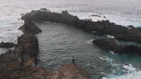 Aerial view. A beautiful bay in the shape of a triangle - the guy stands on a cliff, next to the natural pools. Tenerife. Canary Islands, Spain 2k stock video footage