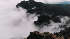 Aerial view - beautiful clouds curl in the gorges of the mountains, view from a high altitude of the valley of volcanic stock footage