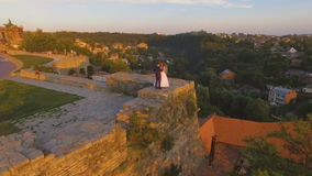 Aerial view: beautiful couple walking at the antique big castle 4k. Aerial view: beautiful wedding couple walking on at the antique castle. 4k stock video footage