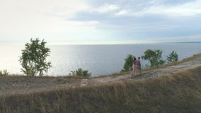 Aerial view on beautiful couple walking on steep rocks. Romantic walk of the couple near the rocks,Loving couple standing on the top of rock. man and woman stock footage