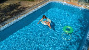 Aerial view of beautiful girl in swimming pool from above, swim on inflatable ring donut and has fun in water on family vacation. On tropical holiday resort stock image