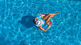 Aerial view of beautiful girl in swimming pool from above, swim on inflatable ring donut and has fun in water. On family vacation Stock Image