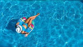 Aerial view of beautiful girl in swimming pool from above, swim on inflatable ring donut and has fun in water Royalty Free Stock Photo