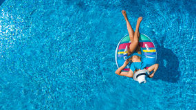 Aerial view of beautiful girl in swimming pool from above, swim on inflatable ring donut and has fun in water. On family vacation Stock Images